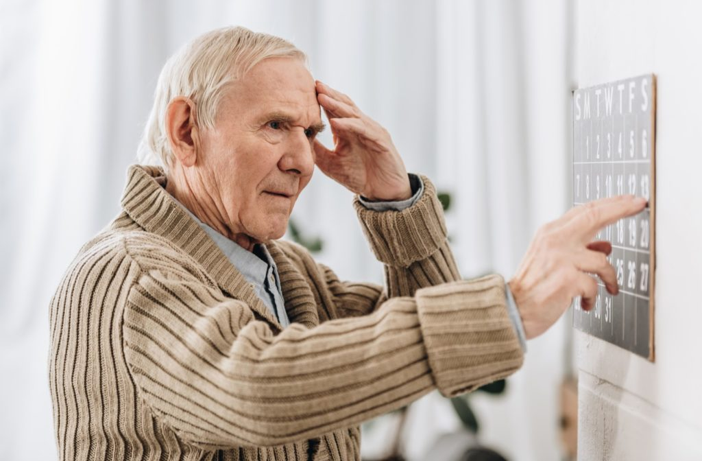 Senior man with dementia looking at wall calendar and touching his head confused.